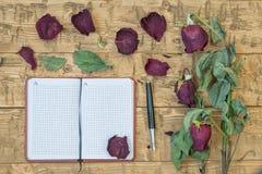 Vissnade rosor med en anteckningsbok och en reservoarpenna på en lantlig tabell Arkivbilder