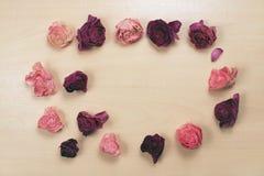 Vissnade rosor på pastellfärgad träbakgrund, bästa sikt Royaltyfri Fotografi