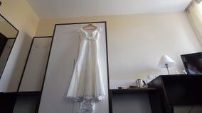 Vist bröllopsklänning på hängare arkivfilmer