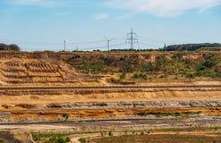 A vista à borda de uma área de mineração com correias transportadoras, energias eólicas do lignite roda no fundo fotos de stock