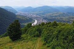 Vista à cidade entre as montanhas O rio flui entre as montanhas com floresta Mizhhirya, Zakarpattya, Ucrânia imagens de stock royalty free