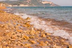 Vista à costa com seixos e areia em Europa Seashell do Scallop na cor-de-rosa litoral da paisagem com as pedras no dia ensolarado Imagens de Stock
