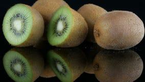 A vista à moda do fruto de quivi cortado e inteiro maduro girou em uma superfície do espelho no fundo preto no estúdio vídeos de arquivo