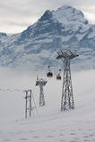 Vista às gôndola do teleférico que movem os esquiadores subida na estância de esqui em Grindelwald, Suíça Fotos de Stock Royalty Free