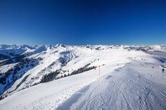 A vista às montanhas e ao esqui alpinos inclina-se em Áustria da estância de esqui de Kitzbuehel Fotos de Stock