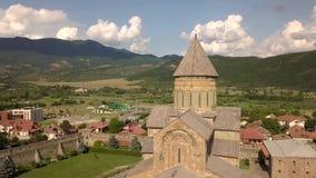 Vista aérea à catedral ortodoxo famosa de Svetitskhoveli e à cidade histórica e turística Mtskheta, perto de Tbilisi, Geórgia filme