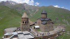 Vista aérea à igreja de trindade de Gergeti perto da vila Gergeti em Geórgia, sob a montagem Kazbegi vídeos de arquivo