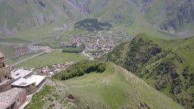 Vista aérea à igreja de trindade de Gergeti perto da vila Gergeti em Geórgia, sob a montagem Kazbegi video estoque