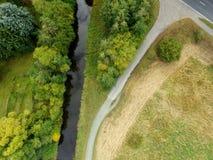Vista aérea abstracta de una corriente enderezada al lado de un prado w Fotos de archivo