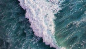 Vista aérea abstrata das ondas de oceano que deixam de funcionar na linha costeira rochosa video estoque