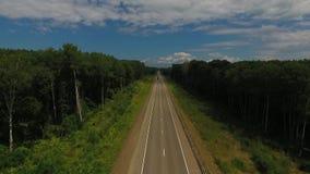 Vista aérea acima da condução de carros ao longo da estrada vazia do campo no dia ensolarado vídeos de arquivo