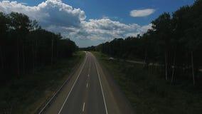 Vista aérea acima da condução de carros ao longo da estrada vazia do campo no dia ensolarado filme