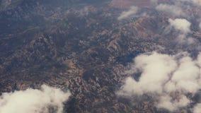 Vista aérea asombrosa de las colinas de la montaña fuera de la ventana plana El viajar por el aire Vista maravillosa de la montañ almacen de video