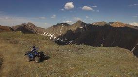 Vista aérea 4x4 ATV que elimina a estrada à parte superior do pico de montanha Altai 4k video estoque