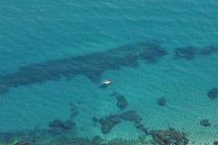 Vista aérea da água azul desobstruída e do barco amarelo foto de stock