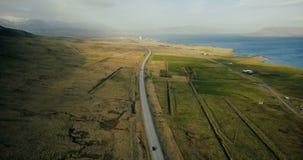 Vista aérea da estrada cênico das montanhas Carros que montam através do campo verde na estrada perto da costa do mar filme
