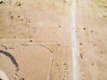 Vista aérea da estrada com carro Vista aérea de uma estrada secundária com areia Carro que passa perto Estrada aérea da construçã fotos de stock royalty free
