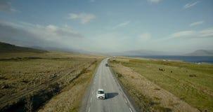 Vista aérea da estrada das montanhas Carros que montam através do campo verde na estrada perto da costa do mar filme