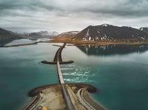 Vista aérea da estrada 1 em Islândia com a ponte sobre o mar na península de Snaefellsnes com nuvens, água e montanha dentro imagem de stock