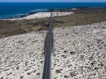 Vista aérea da estrada litoral que cruza as praias e as angras do ³ n Blanco de Mojà e da espiral Caleta Lanzarote, Ilhas Canária imagem de stock