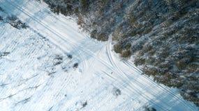 Vista aérea da estrada que passa com a opinião superior da floresta coberto de neve do inverno fotos de stock royalty free