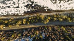 Vista aérea da estrada rural da mola na floresta do pinho amarelo com o lago de derretimento do gelo foto de stock