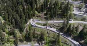 A vista aérea da estrada da serpentina da montanha com condução dos caminhões e de carros no ziguezague vai para cima e para baix filme