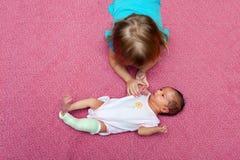 Vista aérea da irmã mais idosa Comforting Newborn Baby que veste a fotografia de stock royalty free