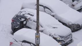 Vista aérea da neve e do gelo da limpeza da mulher fora de sua janela do protetor de vento do carro