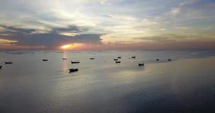 Vista aérea da ponte do molhe que viaja em torno do mar com o por do sol bonito que mostra barcos na superfície da água, tiro do  vídeos de arquivo