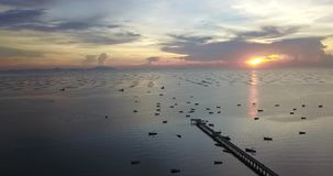 Vista aérea da ponte do molhe que viaja em torno do mar com o por do sol bonito que mostra barcos na superfície da água, tiro do  video estoque