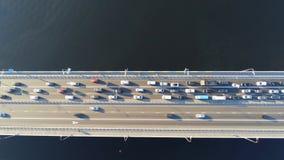 Vista aérea da ponte da estrada através do rio com doce do trânsito intenso em um sentido Horas de ponta com erva-benta e sobreca filme
