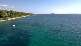 A vista aérea da praia azul impressionante abaixo de um monte na área de Halkidiki Grécia, abaixa para a frente e pelo zangão vídeos de arquivo