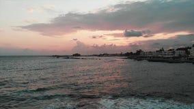 Vista aérea da torre do salvamento no por do sol com ondas de oceano e porto da cidade no fundo vídeos de arquivo