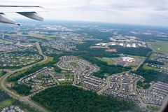 Vista aérea das casas da residência tomadas do avião de voo no fundo do borrão imagem de stock
