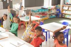 Vista aérea das crianças da escola que levantam a mão para responder da pergunta do professor foto de stock