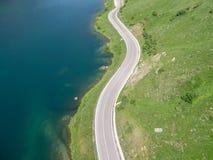 Vista aérea das montanhas da rua com lago Fotografia de Stock Royalty Free