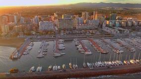 Vista aérea de barcos en el puerto, con los edificios de la ciudad detrás almacen de video