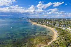 Vista aérea de Brighton Bathing Boxes y de Melbourne CBD fotos de archivo