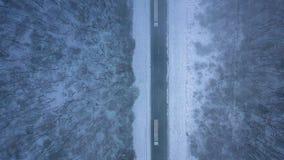 Vista aérea de camiones en el camino que pasa a través del bosque del invierno en ventisca almacen de video