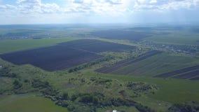 Vista aérea de campos arados y sembrados cerca del pueblo o de las casas de los granjeros en día de verano soleado contra el ciel metrajes