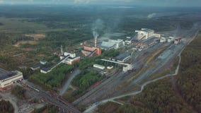 Vista aérea de construções industriais da planta com as chaminés altas cercadas pelo sistema de produção da floresta filme