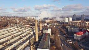 Vista aérea de distritos de una ciudad con las fábricas de los tubos, cuyo hay humo metrajes