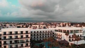 Vista aérea de hoteles y de edificios en la puesta del sol Tiro aéreo del abejón del hotel con la piscina y las palmas metrajes