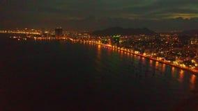 Vista aérea de la bahía oscura del océano y de la ciudad distante de la noche almacen de video