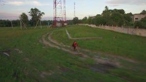 Vista aérea de la bici del montar a caballo del muchacho en el campo almacen de metraje de vídeo