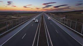 Vista aérea de la carretera y de la puesta del sol dramática Coches, gente que viaja en todo el mundo concepto almacen de metraje de vídeo