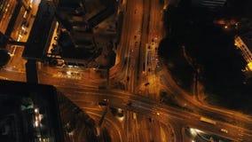 Vista aérea de la ciudad en la noche con los edificios modernos, la intersección de la carretera y los coches móviles existencias almacen de metraje de vídeo