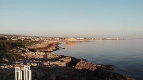 Vista aérea de la ciudad de Paphos con el monumento blanco en la playa rocosa durante puesta del sol Naturaleza de Chipre almacen de metraje de vídeo