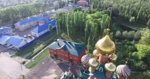 Vista aérea de la iglesia ortodoxa roja con las bóvedas de oro iglesia de la Rojo-piedra del helicóptero La iglesia se rodea cerc metrajes